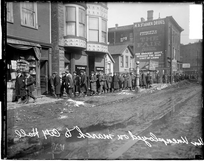 Parade of unemployed men marching to City Hall, view looking west on West 14th Street in front of Myron D. Staiger Drugs. Group portrait of parade of unemployed men marching to City Hall. On the right of the image, Myron D. Staiger Drugs Store is visible, located at 1356 South Racine. Harry Feldman's Barber Shop, located at 1214 West 14th Street is also visible in the background, located in the Near West Side community area of Chicago, Illinois. Source: DN-0062263, Chicago Daily News negatives collection, Chicago History Museum. Date: 1914 Mar.