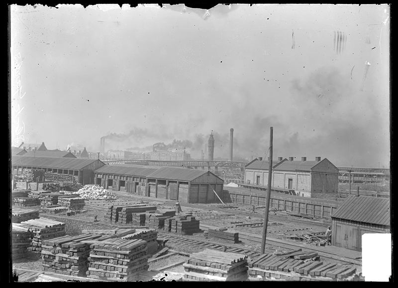 Railroad yard at the rear of the Union Stock Yards. View of a railroad yard at the rear of the Union Stock Yards in Chicago, Illinois, showing various large storage buildings, railroad tracks and piles of lumber and building materials. An Armour and Company building, a Swift and Company building, a bridge and smoke billowing from smokestacks are visible in the background. Source: DN-0000163, Chicago Daily News negatives collection, Chicago History Museum. Date: ca. 1902.