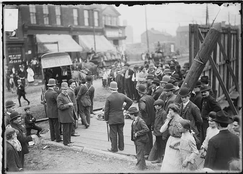 Crowd, including women and children, gathered along a road with police and horse-drawn carriages during the 1904 Stockyards Strike. Image of a crowd, including women and children, gathered along a road with police and horse-drawn carriages during the 1904 Stockyards Strike in the New City community area of Chicago, Illinois. Source: DN-0000936, Chicago Daily News negatives collection, Chicago History Museum. Date: ca. 1904 July 7-Sept. 9.