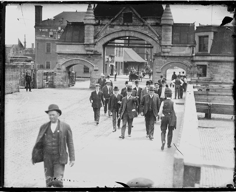 Unidentified group of men walking away from the Union Stock Yards Gate. Image of an unidentified group of men walking away from the Union Stock Yards Gate at 850 West Exchange Avenue in the New City community area of Chicago, Illinois. The gate was built in 1879. Source: DN-0050344, Chicago Daily News negatives collection, Chicago History Museum. Date: ca. 1906.