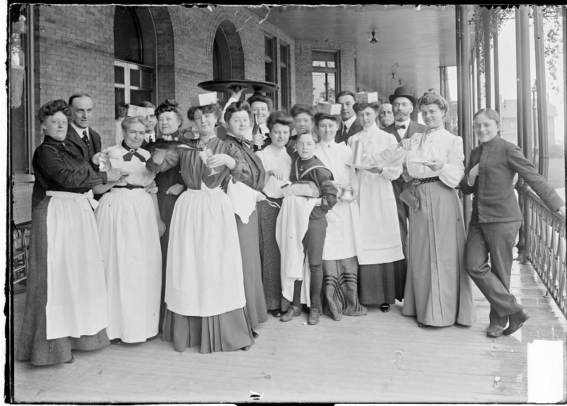 Large group of guests dressed as wait staff assembled on a Chicago Beach hotel porch during a Waiters strike. Image of guests dressed as wait staff assembled on a Chicago Beach hotel porch during a Waiters strike in Chicago Illinois. Some are holding trays with bread or bottles and glasses. Source: DN-0000637, Chicago Daily News negatives collection, Chicago History Museum. Date: 1903 June 6.