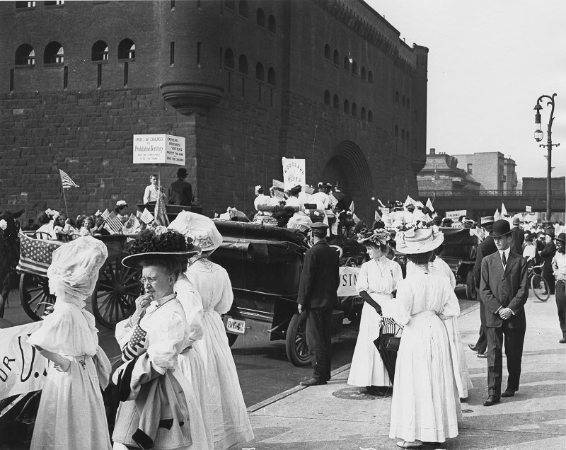Women looking on as a parade is about to begin. Description: Women looking on as a parade is about to begin; Chicago, IL. Source: ICHi-52247. Chicago History Museum. Reproduction of photographic print, photographer C. R. Childs. Date: unknown.